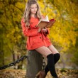 Beautiful elegant girl with orange coat reading sitting on a stump autumnal park. Young pretty woman with blonde hair spending time in fall. Long legs sensual blonde relaxing with a book in forest — Stock Photo #56410355