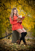 Beautiful elegant girl with orange coat reading sitting on a stump autumnal park. Young pretty woman with blonde hair spending time in fall. Long legs sensual blonde relaxing with a book in forest — Stock Photo