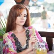 Attractive red hair young woman with bright colored blouse drinking lemonade on a terrace. Gorgeous redhead model drinking fresh drink with straw in a summer day — Stock Photo #56424685