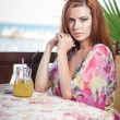 Attractive red hair young woman with bright colored blouse drinking lemonade on a terrace having blue sea in background. Gorgeous redhead model drinking fresh drink with straw in a summer day — Stock Photo #56424693