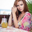 Attractive red hair young woman with bright colored blouse drinking lemonade on a terrace having blue sea in background. Gorgeous redhead model drinking fresh drink with straw in a summer day — Stock Photo #56424695