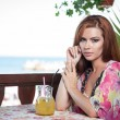 Attractive red hair young woman with bright colored blouse drinking lemonade on a terrace having blue sea in background. Gorgeous redhead model drinking fresh drink with straw in a summer day — Stock Photo #56424701
