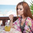 Attractive red hair young woman with bright colored blouse drinking lemonade on a terrace having blue sea in background. Gorgeous redhead model drinking fresh drink with straw in a summer day — Stock Photo #56424703