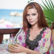 Attractive red hair young woman with bright colored blouse drinking lemonade on a terrace having blue sea in background. Gorgeous redhead model drinking fresh drink with straw in a summer day — Stock Photo #56424705