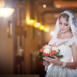 Young beautiful luxurious woman in wedding dress posing in luxurious interior. Bride with long veil holding her wedding bouquet. Seductive blonde bride with fashionable gown, indoor shot — Photo #56751881