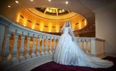 Young beautiful luxurious woman in wedding dress posing in luxurious interior. Bride with huge wedding dress in majestic manor. Seductive blonde bride with gorgeous gown and long dally posing — Stock Photo