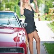 Summer portrait of stylish blonde vintage woman with long legs posing near red retro car. fashionable attractive fair hair female with black hat near a red vehicle. Sunny bright colors, outdoors shot. — Stockfoto #57056631