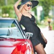 Summer portrait of stylish blonde vintage woman with long legs posing near red retro car. fashionable attractive fair hair female with black hat near a red vehicle. Sunny bright colors, outdoors shot. — Stok fotoğraf #57056633