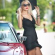 Summer portrait of stylish blonde vintage woman with long legs posing near red retro car. fashionable attractive fair hair female with black hat near a red vehicle. Sunny bright colors, outdoors shot. — Stock Photo #57056635