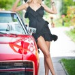 Summer portrait of stylish blonde vintage woman with long legs posing near red retro car. fashionable attractive fair hair female with black hat near a red vehicle. Sunny bright colors, outdoors shot. — Stok fotoğraf #57056637