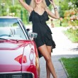 Summer portrait of stylish blonde vintage woman with long legs posing near red retro car. fashionable attractive fair hair female with black hat near a red vehicle. Sunny bright colors, outdoors shot. — Stok fotoğraf #57056639