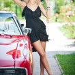 Summer portrait of stylish blonde vintage woman with long legs posing near red retro car. fashionable attractive fair hair female with black hat near a red vehicle. Sunny bright colors, outdoors shot. — Stok fotoğraf #57056651