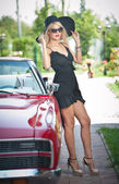 Summer portrait of stylish blonde vintage woman with long legs posing near red retro car. fashionable attractive fair hair female with black hat near a red vehicle. Sunny bright colors, outdoors shot. — Stock Photo