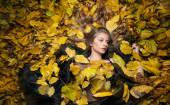 Nice girl covered with autumnal leaves. Young woman laying down on the ground covered by fall foliage in park. Beautiful sexy girl lying on autumn leaves. Young woman covered with golden autumn leaves — Fotografia Stock