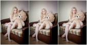 Young blond sensual woman sitting on sofa relaxing with a huge teddy bear. Beautiful girl with comfortable clothes relaxing on the couch with a toy. Attractive blonde in cozy scenery indoor — Stock Photo