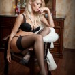 Attractive and sexy blonde woman with black bra and long stockings posing provocatively sitting on a chair. Beautiful woman with long fair hair and high heels wearing black lingerie in vintage room — Stock Photo #57598955