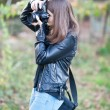 Attractive young girl taking pictures outdoors. Cute teenage girl in blue jeans and black leather jacket taking photos in autumnal park. Outdoor portrait of pretty teen having fun in park with camera — Stock Photo #57766771