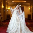 Young beautiful luxurious woman in wedding dress posing in luxurious interior. Gorgeous elegant bride with long veil. Full length portrait of seductive blonde bride with fashionable gown, indoor shot — Stock Photo #57935543