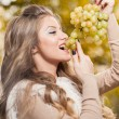 Young woman eating grapes outdoor. Sensual blonde female smiling holding a bunch of green grapes. Beautiful fair hair girl eating healthy fruits. Pretty woman holding a ripe grapes bunch — Stock Photo #58155827