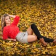 Beautiful elegant woman with red blouse and short skirt posing in park during fall. Young pretty woman with blonde hair lying down on autumnal leaves. Sensual blonde with black leggings in forest. — Stock Photo #58155829