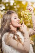 Young woman eating grapes outdoor. Sensual blonde female smiling holding a bunch of green grapes. Beautiful fair hair girl eating healthy fruits. Pretty woman holding a ripe grapes bunch — Stock Photo