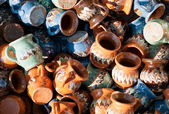 Romanian traditional pottery handcrafted mugs at a souvenir shop. Romanian traditional handcrafted pottery plates and jugs — Stockfoto