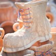 Ceramic shoes with tricolor laces for sale at a souvenir market in Romania — Stock Photo #58666699