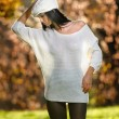 Beautiful sexy girl in white posing in park in autumn day. Beautiful elegant woman with white cap in autumnal park. Young pretty brunette woman with leggings and long legs in the forest — Stock Photo #58725101