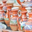 Romanian traditional pottery handcrafted mugs at a souvenir shop. Romanian traditional handcrafted pottery plates and jugs — Stock Photo #58760977
