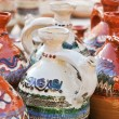 Romanian traditional pottery handcrafted mugs at a souvenir shop. Romanian traditional handcrafted pottery jugs to be sold at the market — Stock Photo #59136401