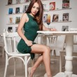 Fashionable attractive young woman in green dress sitting in restaurant. Beautiful redhead posing in elegant scenery with an orange juice glass on the table. Pretty female relaxing, indoor shot. — Stock Photo #59680235