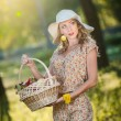 Attractive young woman in a summer fashion shot. Beautiful fashionable young girl with straw basket and hat in park near a tree in sunshine. Blonde woman posing in forest in a sunny day, outdoor shot — Stok fotoğraf #59699473