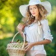 Attractive young woman in a summer fashion shot. Beautiful fashionable young girl with straw basket and hat in park near a tree in sunshine. Blonde woman posing in forest in a sunny day, outdoor shot — Stok fotoğraf #59754801