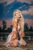 Gorgeous blonde woman in transparent blouse posing provocatively in front of a beautiful sunset. Fair hair girl baring her shoulder and legs in front of lake on cloudy sky background. — Stock Photo
