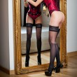 Attractive woman in red lingerie posing challenging near a large mirror. Sensual woman with long legs and high heels in corset. Classic boudoir shot. Erotic photo. — Stock Photo #60275047