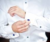 Man wears cuff-links on a shirt sleeve. A groom putting on cuff-links as he gets dressed in formal wear. Groom's suit — Stock Photo