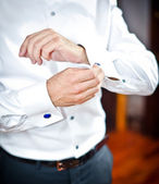 Man wears cuff-links on a shirt sleeve. A groom putting on cuff-links as he gets dressed in formal wear. Groom's suit — Стоковое фото