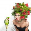 Beautiful creative Xmas makeup and hair style indoor shot. Beauty Fashion Model Girl. Winter. Beautiful attractive girl with Christmas tree accessories in studio speaking with a green parrot. — Stock Photo #60963695