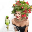 Beautiful creative Xmas makeup and hair style indoor shot. Beauty Fashion Model Girl. Winter. Beautiful attractive girl with Christmas tree accessories in studio speaking with a green parrot. — Stock Photo #60963703