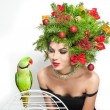 Beautiful creative Xmas makeup and hair style indoor shot. Beauty Fashion Model Girl. Winter. Beautiful attractive girl with Christmas tree accessories in studio speaking with a green parrot. — Stock Photo #60963707