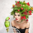 Beautiful creative Xmas makeup and hair style indoor shot. Beauty Fashion Model Girl. Winter. Beautiful attractive girl with Christmas tree accessories in studio speaking with a green parrot. — Stock Photo #60963715