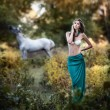 Young women in a blue long skirt and white bra at sunset in forest with a white horse in background .Beautiful young woman with long hair in garden with wild horse. Girl and horse in the field — Stock Photo #61074325
