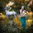 Young women in a blue long skirt and white bra at sunset in forest with a white horse in background .Beautiful young woman with long hair in garden with wild horse. Girl and horse in the field — Stock Photo #61074327