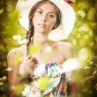 Young beautiful brunette woman wearing a large hat in a sunny day. Portrait of attractive long hair female with multicolored blouse, outdoor shot in a garden. Pretty girl enjoying the nature in summer — Stock Photo #61074331