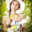 Young beautiful brunette woman wearing a large hat in a sunny day. Portrait of attractive long hair female with multicolored blouse, outdoor shot in a garden. Pretty girl enjoying the nature in summer — Stock Photo #61074339