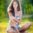 Young beautiful long hair woman wearing a multicolored dress posing on a stump in a green forest. Fashionable sexy attractive girl sitting on hub in a sunny day. Gorgeous girl in garden in summer day. — Stock Photo #61074341