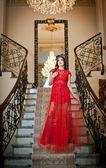 красивая девушка в давно красном платье позирует в старинных сцены. молодая красивая женщина, носить красное платье в старом отеле. чувственный элегантный молодая женщина в красном платье длинные крытый выстрел. — Стоковое фото