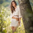 Attractive young woman in white short dress posing near a tree in a sunny summer day. Beautiful girl enjoying the nature in a green forest. Portrait of sensual female in white daydreaming in a meadow — Stock Photo #61217911