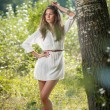 Attractive young woman in white short dress posing near a tree in a sunny summer day. Beautiful girl enjoying the nature in a green forest. Portrait of sensual female in white daydreaming in a meadow — Stock Photo #61217913