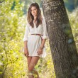 Attractive young woman in white short dress posing near a tree in a sunny summer day. Beautiful girl enjoying the nature in a green forest. Portrait of sensual female in white daydreaming in a meadow — Stock Photo #61217915
